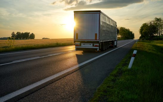 Truck departing towards the horizon on an asphalt road in a rural countryside at sunset.